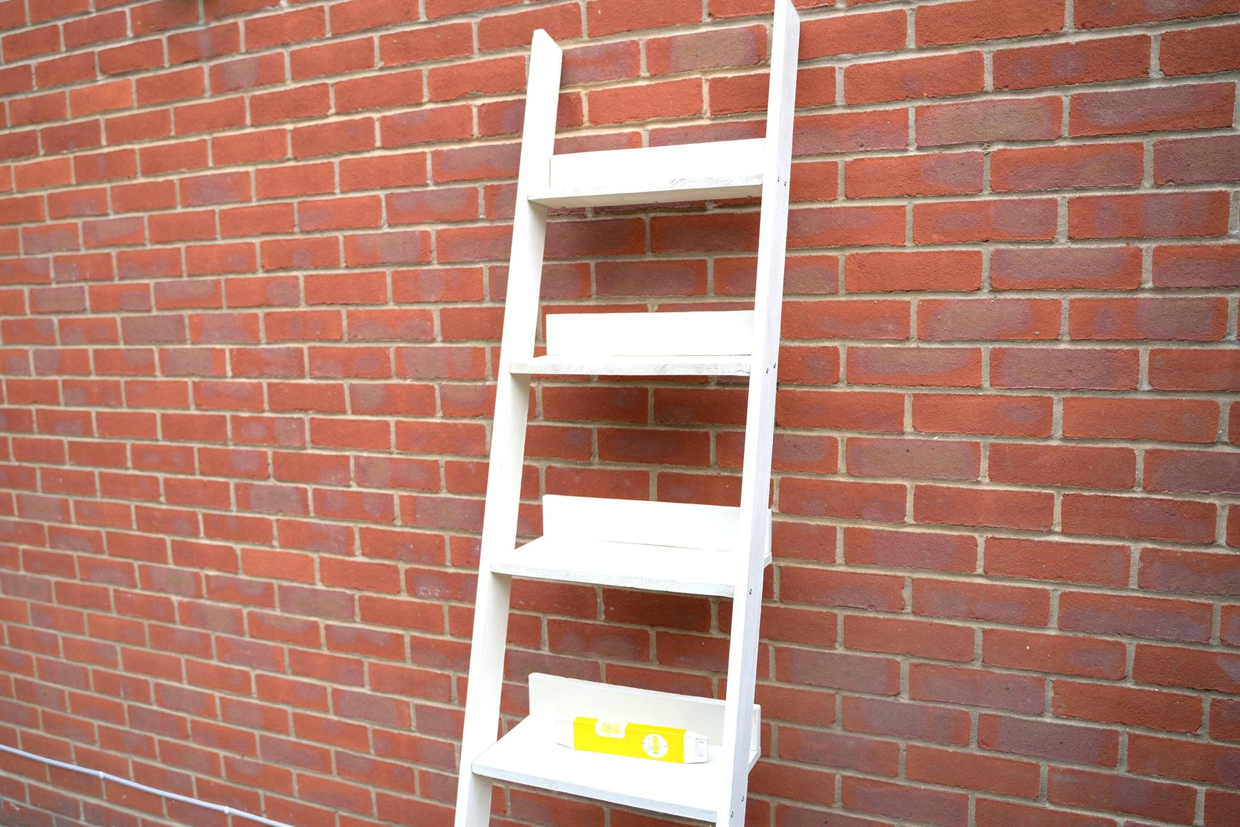 An assembled wooden ladder shelf propped against a wall