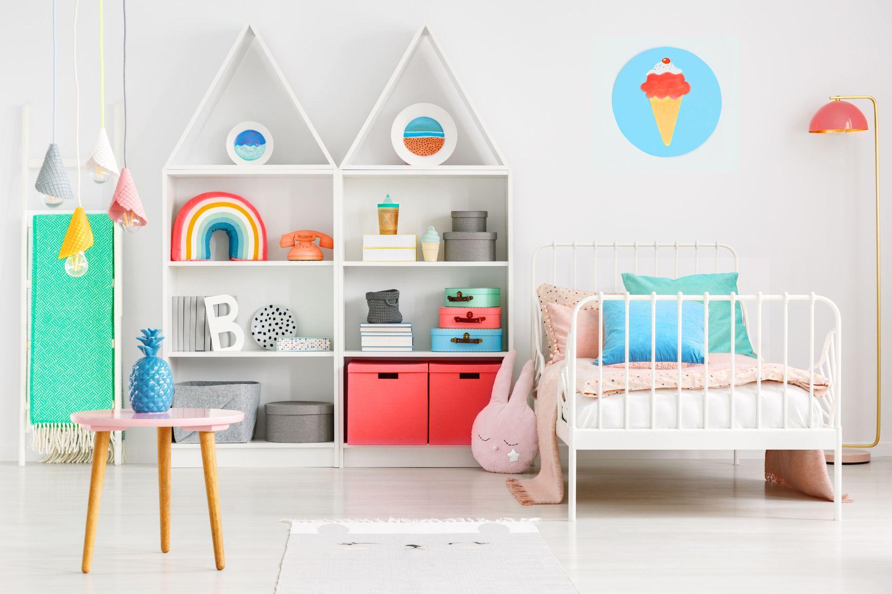 chambre d'enfants avec lit blanc et bibliothèque et objets colorés