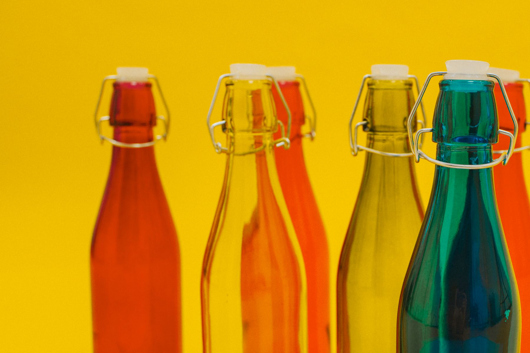 Coloured glass bottles against yellow backdrop
