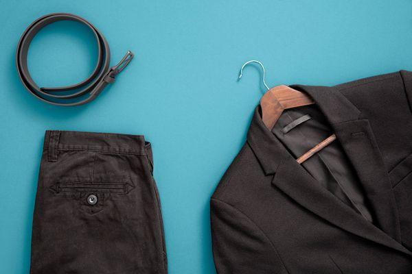 um paletó e uma calça social pretos e um cinto masculinos sobre fundo azul
