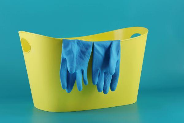 żółte wiadro i niebieskie rękawice gumowe na zielonym tle