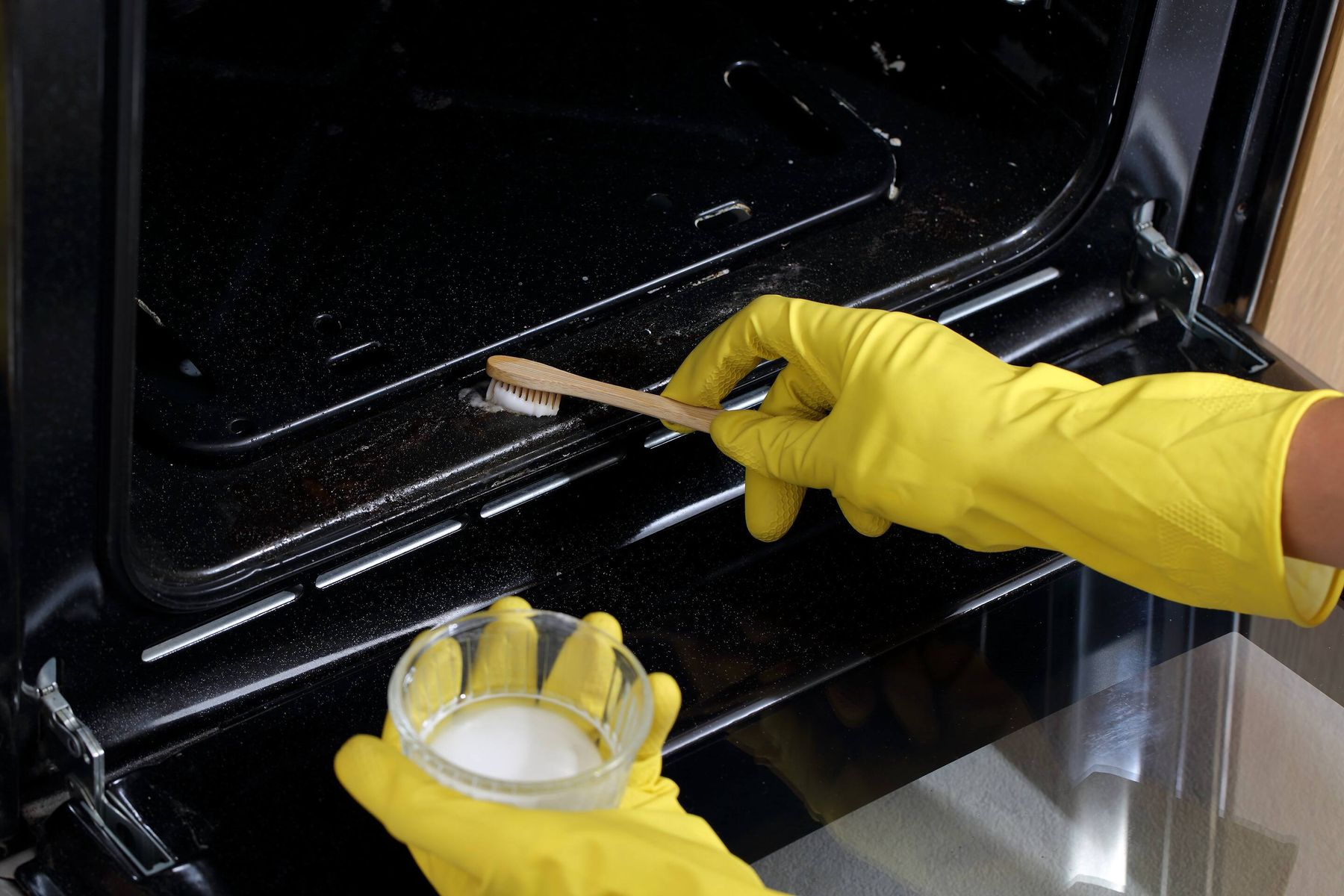 hands brushing mixture to oven interior