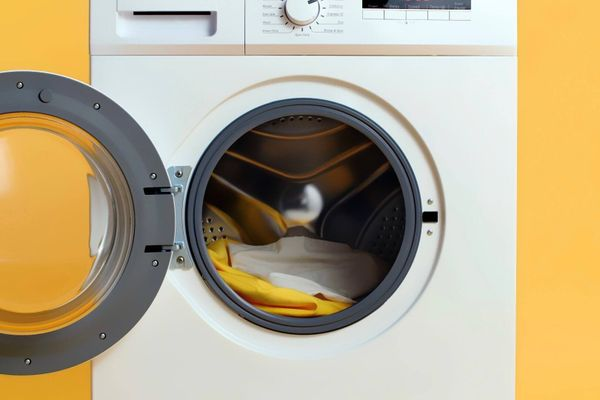 a washing machine on a yellow background