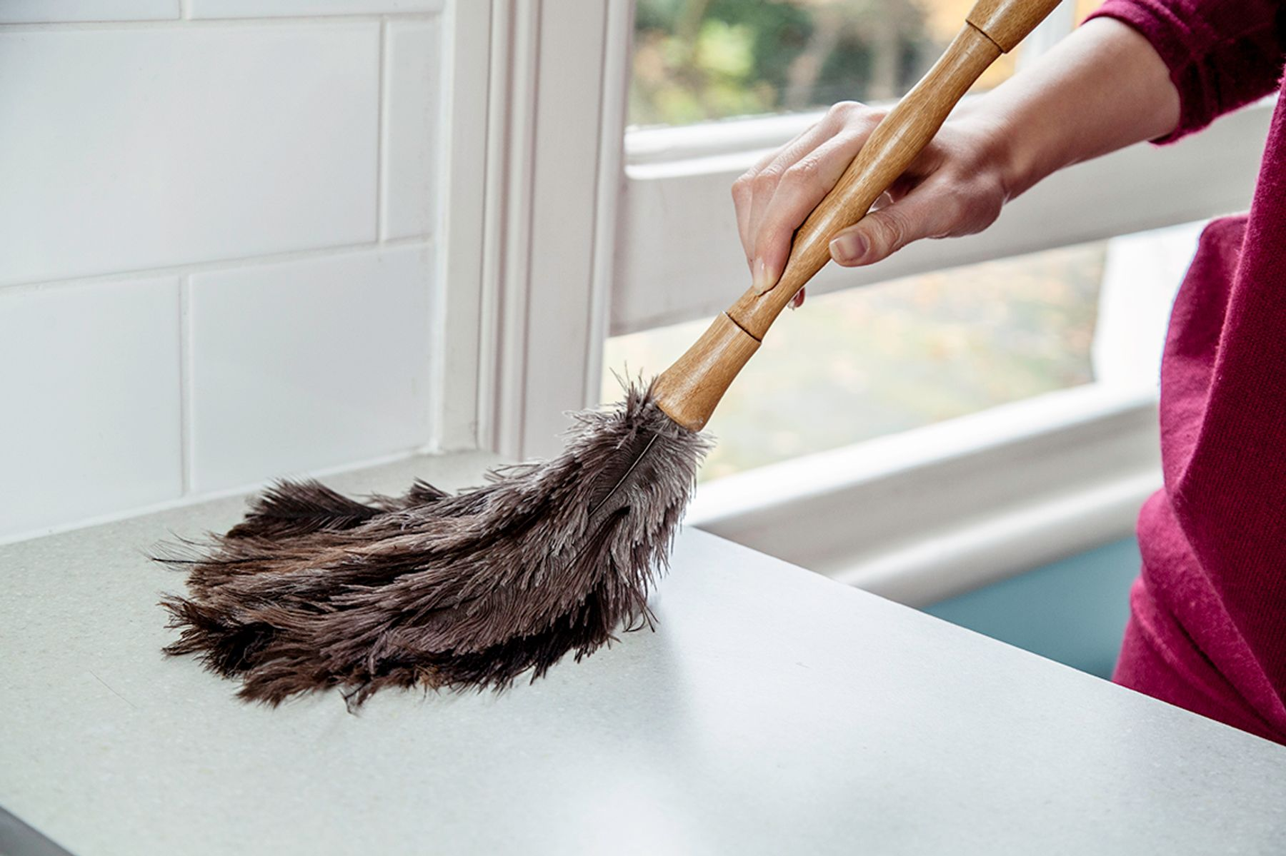 Step 7: A hand using a feather duster on a surface to freshen up when a house smells musty after vacation