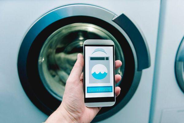 En hand håller i en smartphone med en tvättmaskinsapp framför en smart tvättmaskin