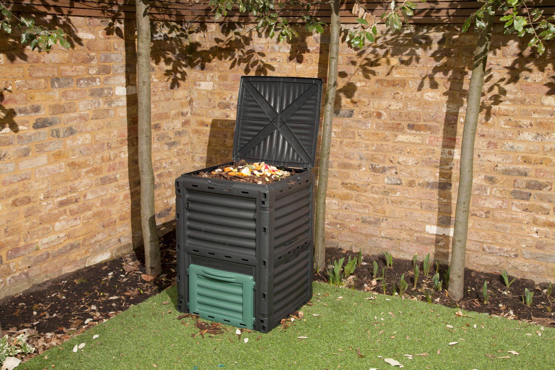 composteira cinza em canto de jardim com parede de tijolinho