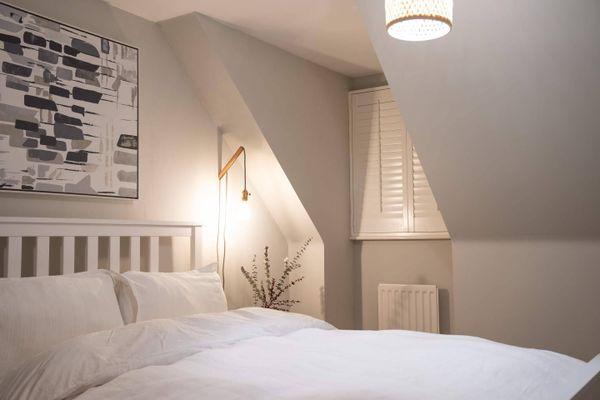 Schlafzimmer mit weißem Bett und Bild an der Wand hängen