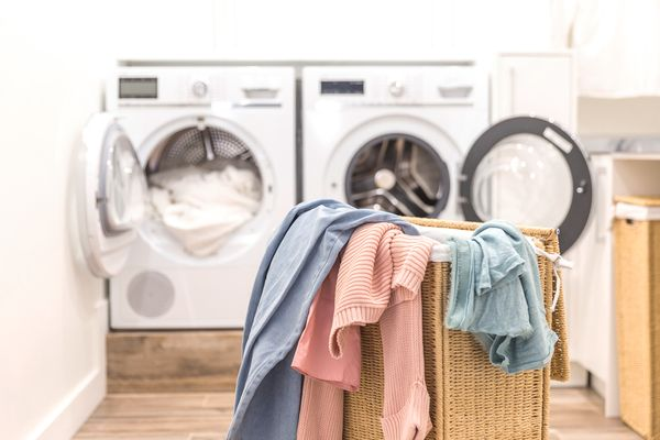 Image of laundry on foreground with washing machine in background