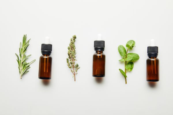 Three bottles of essential oils between three different types of herb against white background