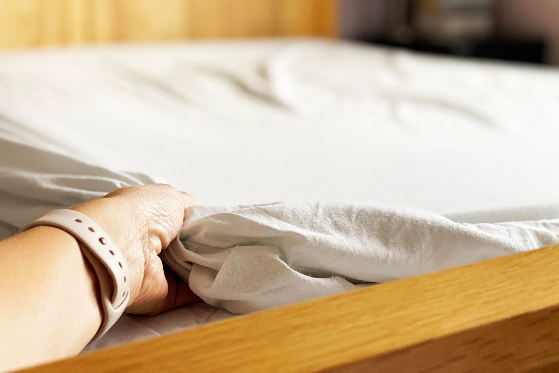 A fitted bedsheet being put on a bed