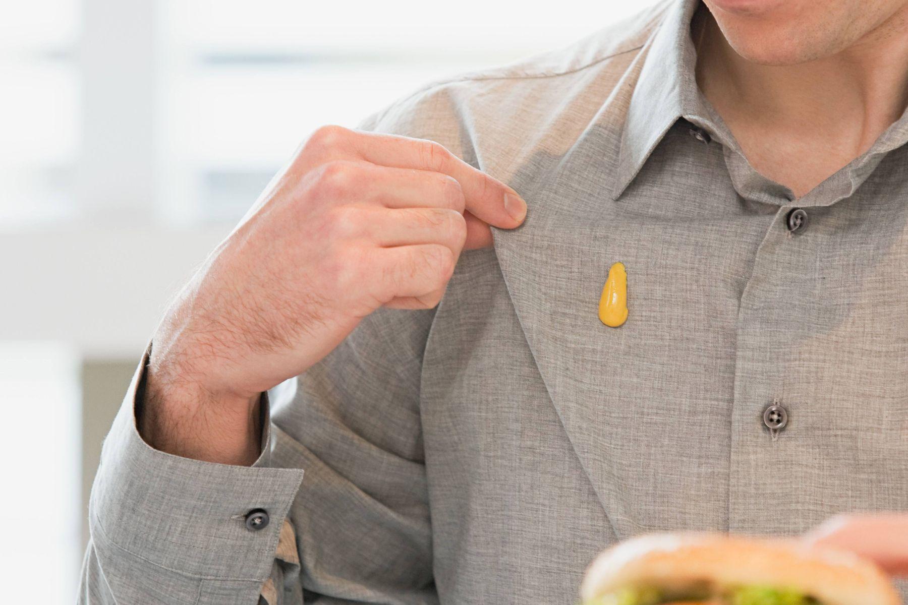 Homem com camisa suja com mancha de mostarda