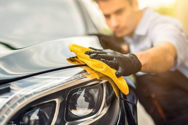 Pessoa polindo o carro com flanela amarela e luvas pretas