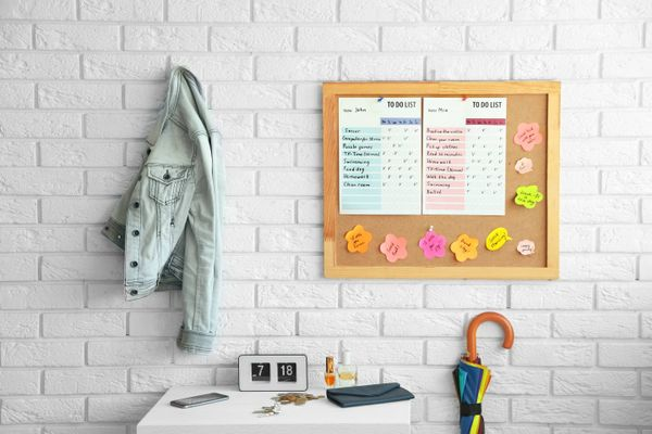 Wooden board with to do list hanging on white brick wall