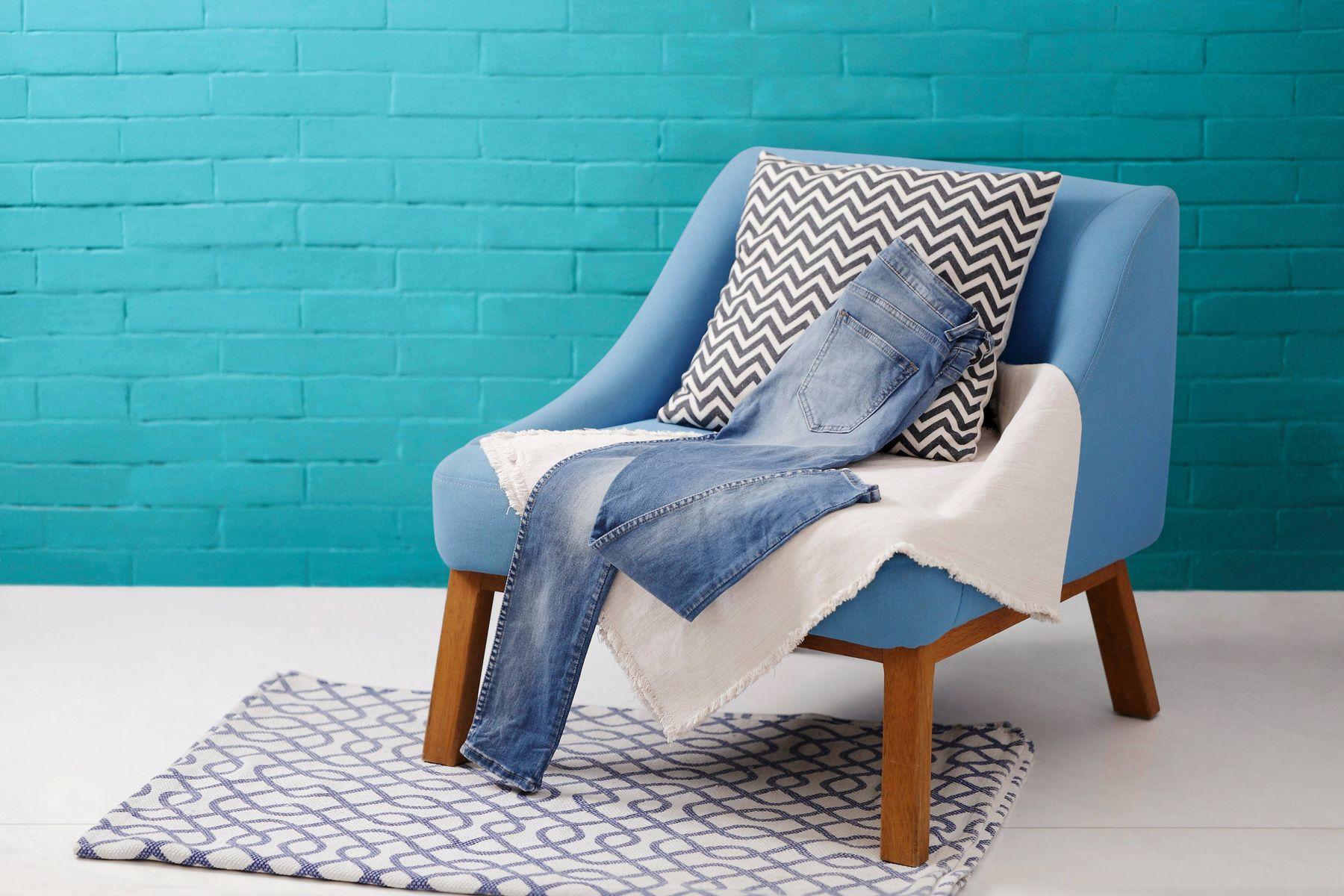 calça jeans sobre poltrona azul com almofada preta e branca e chão branco e parede azul