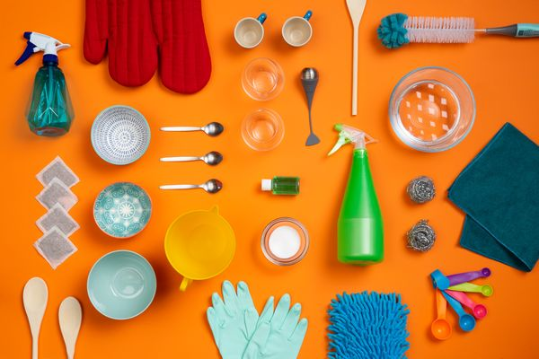 flat lay of cleaning supplies on an orange background