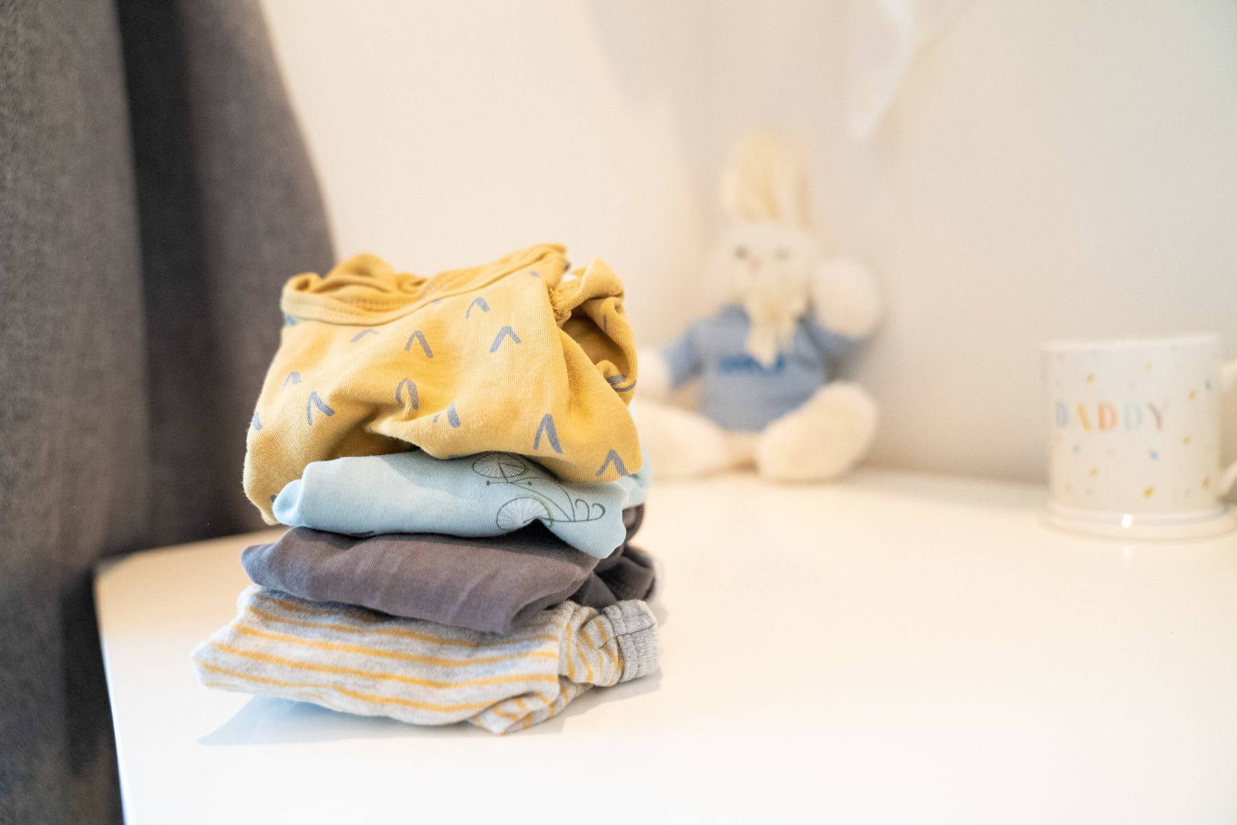 a pile of folded clothes next to a toy