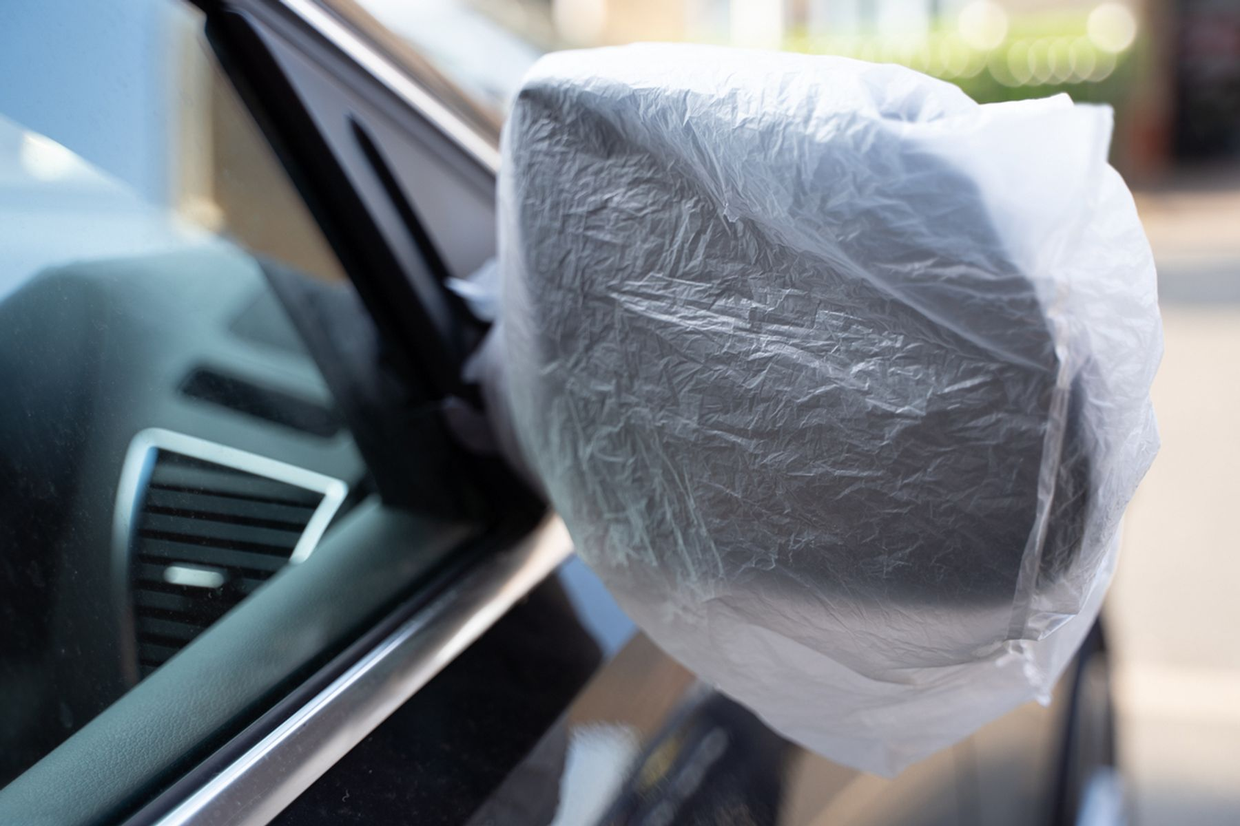 A plastic bag wrapped around a car's wing mirror