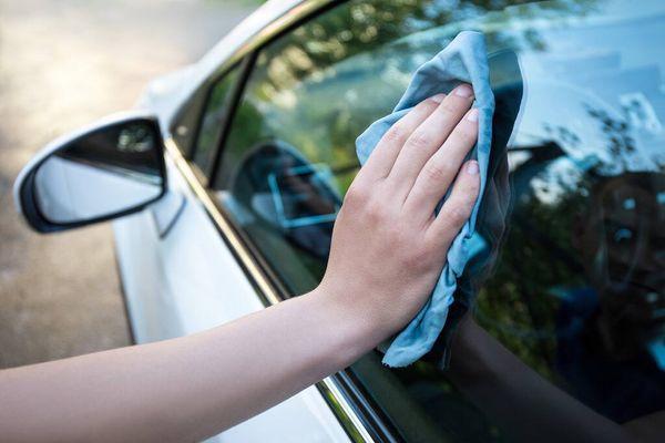 mano con un paño limpiando los vidrios del auto