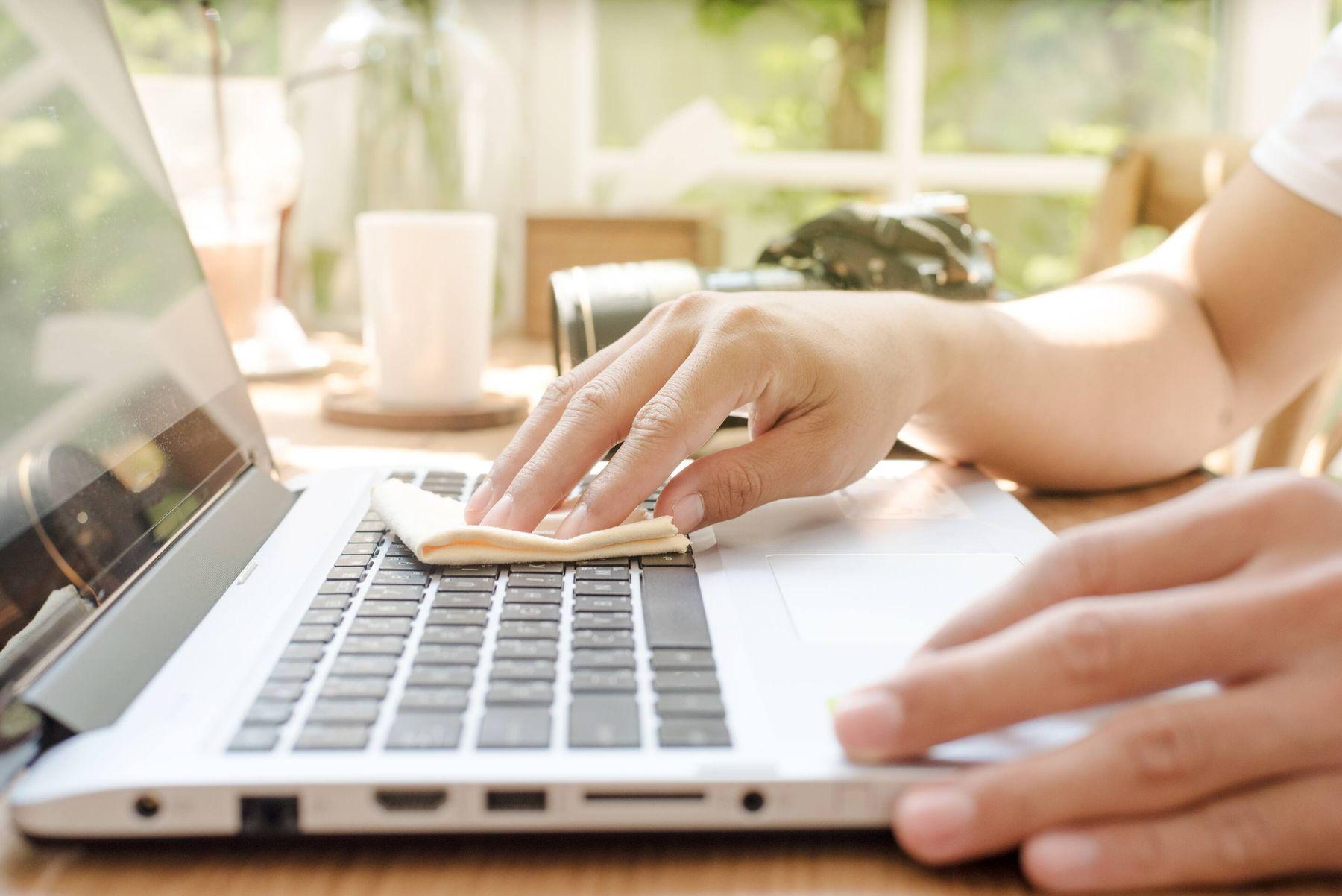 Dùng khăn microfiber lau bề mặt bàn phím laptop và touchpad