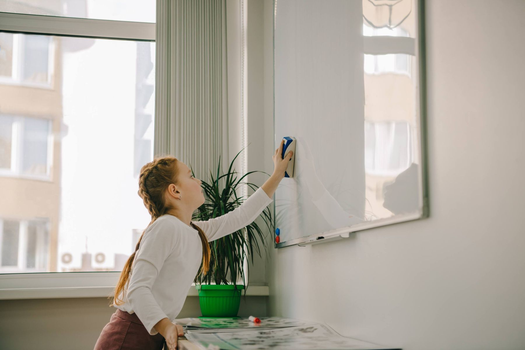 a girl cleaning a whiteboard