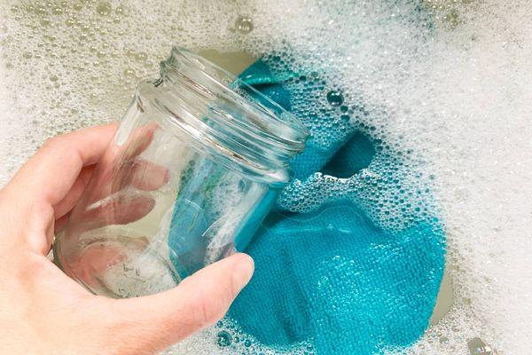 barattolo di vetro in un lavandino pieno d'acqua e di sapone