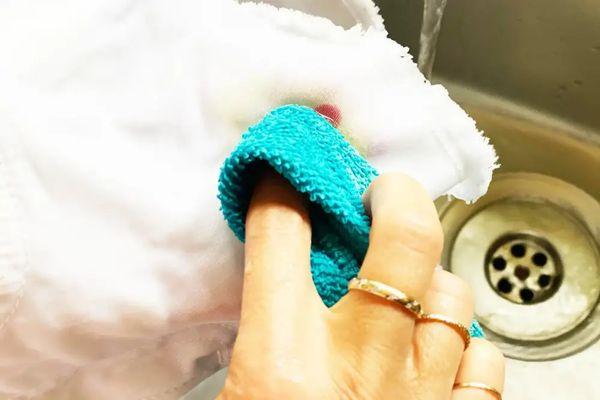 Beyaz giysideki kan lekesini mavi bez, su ve sabunla temizleyen biri