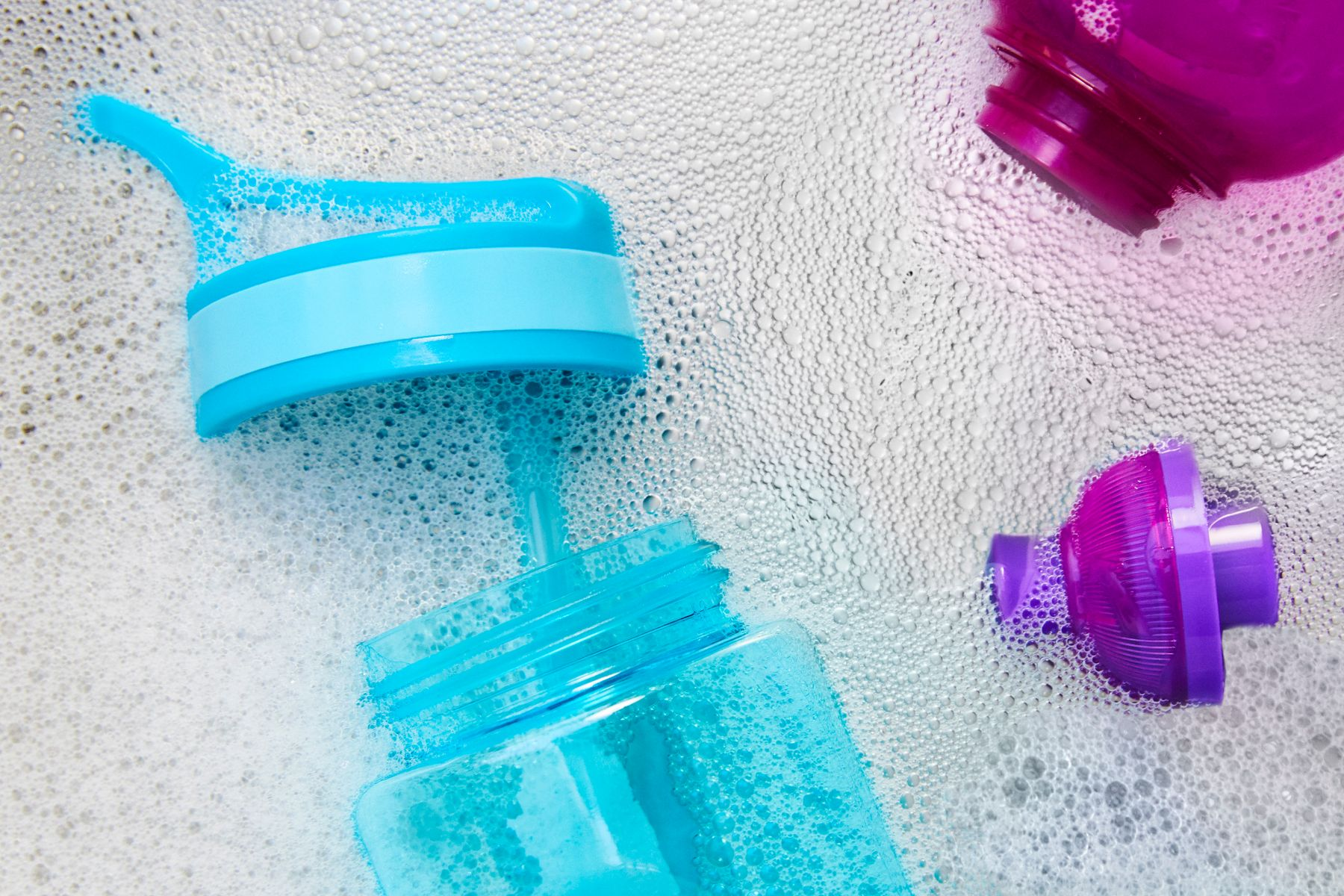 a turquoise and a purple reusable water bottle in soapy water