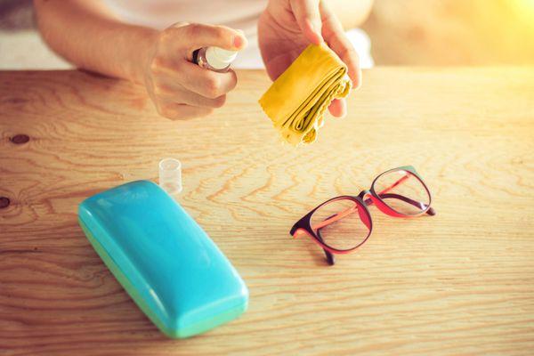 lunettes, chiffon de nettoyage et mains tenant un liquide de pulvérisation
