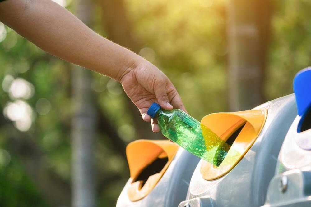 mano de persona tirando una botella plástica dentro de un contenedor de reciclaje