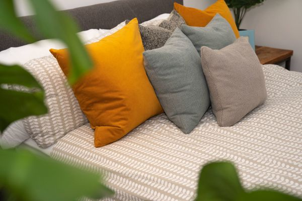 Neatly made bed with cushions on it
