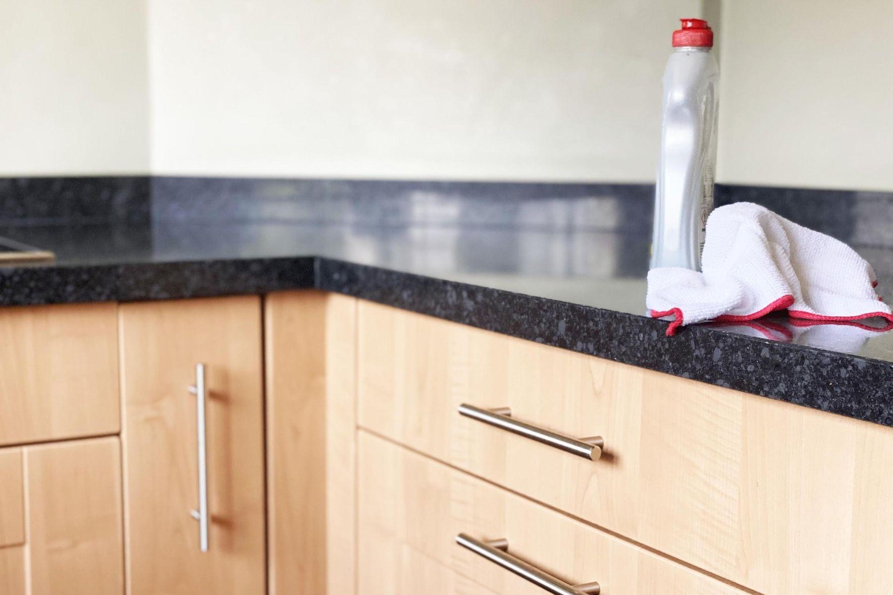 Bancada da cozinha com pano e limpador multiuso