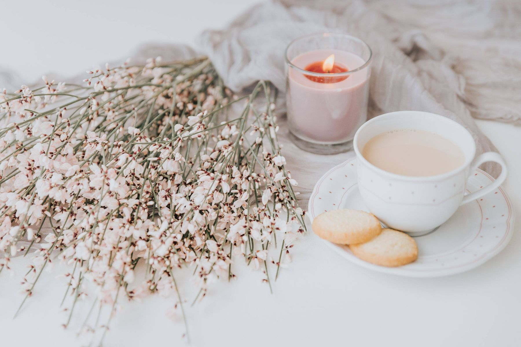 flowers, candle and cup of milk with cookies