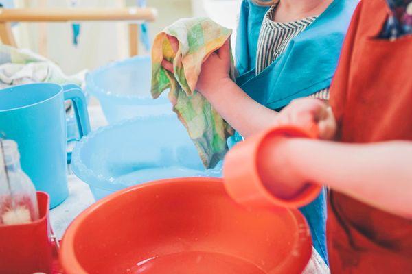 bambini che lavano utensili di plastica