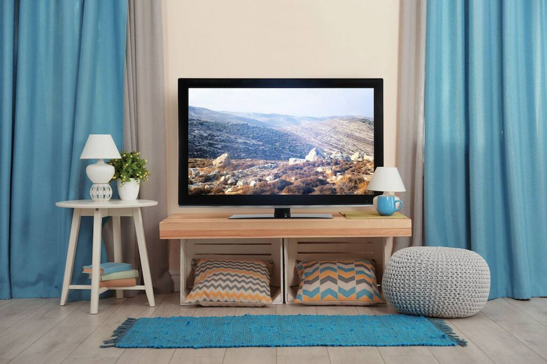 a living room with blue curtains and a TV on a wooden table