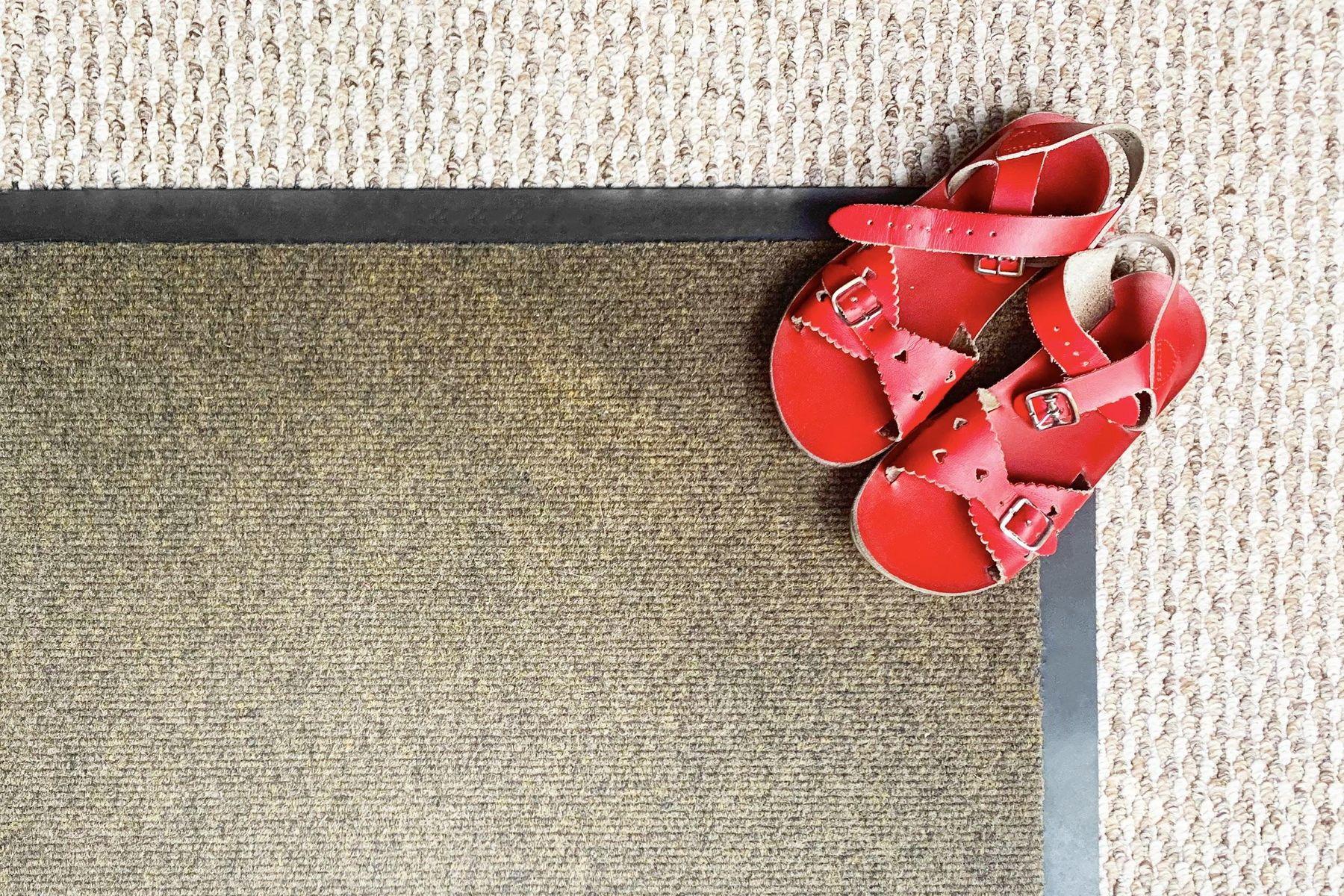 Tapete escuro em cima de um carpete claro e sandálias vermelhas em cima do tapete