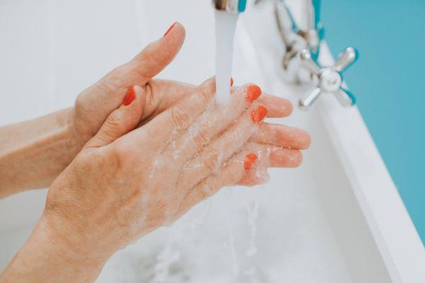 Kobieta myje jej ręce w zlewie