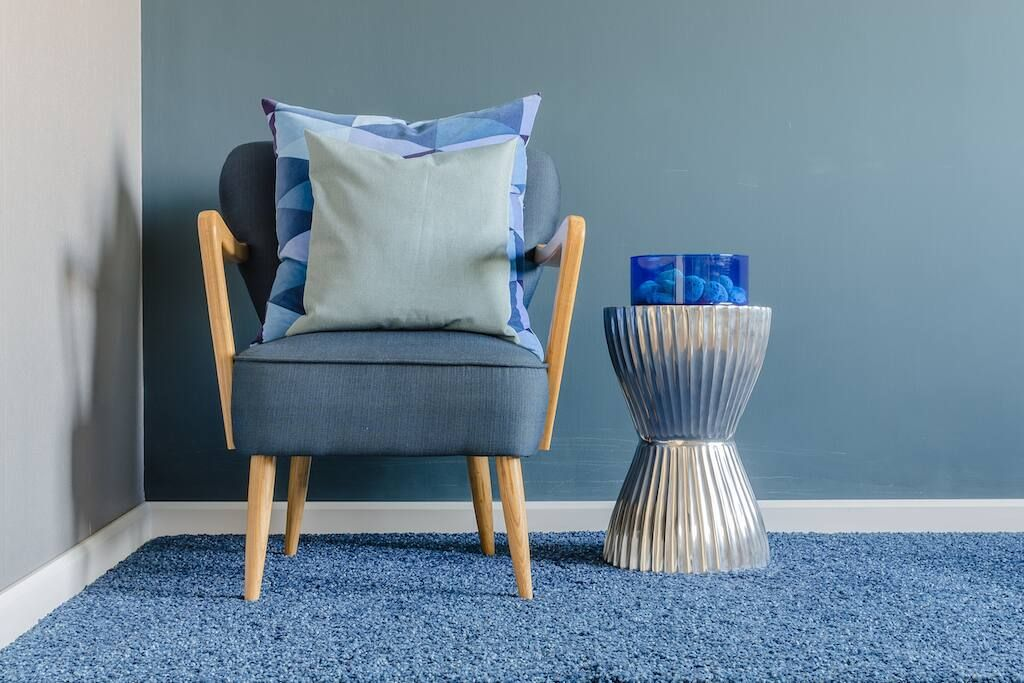 grey blue armchair and table positioned on dry carpet