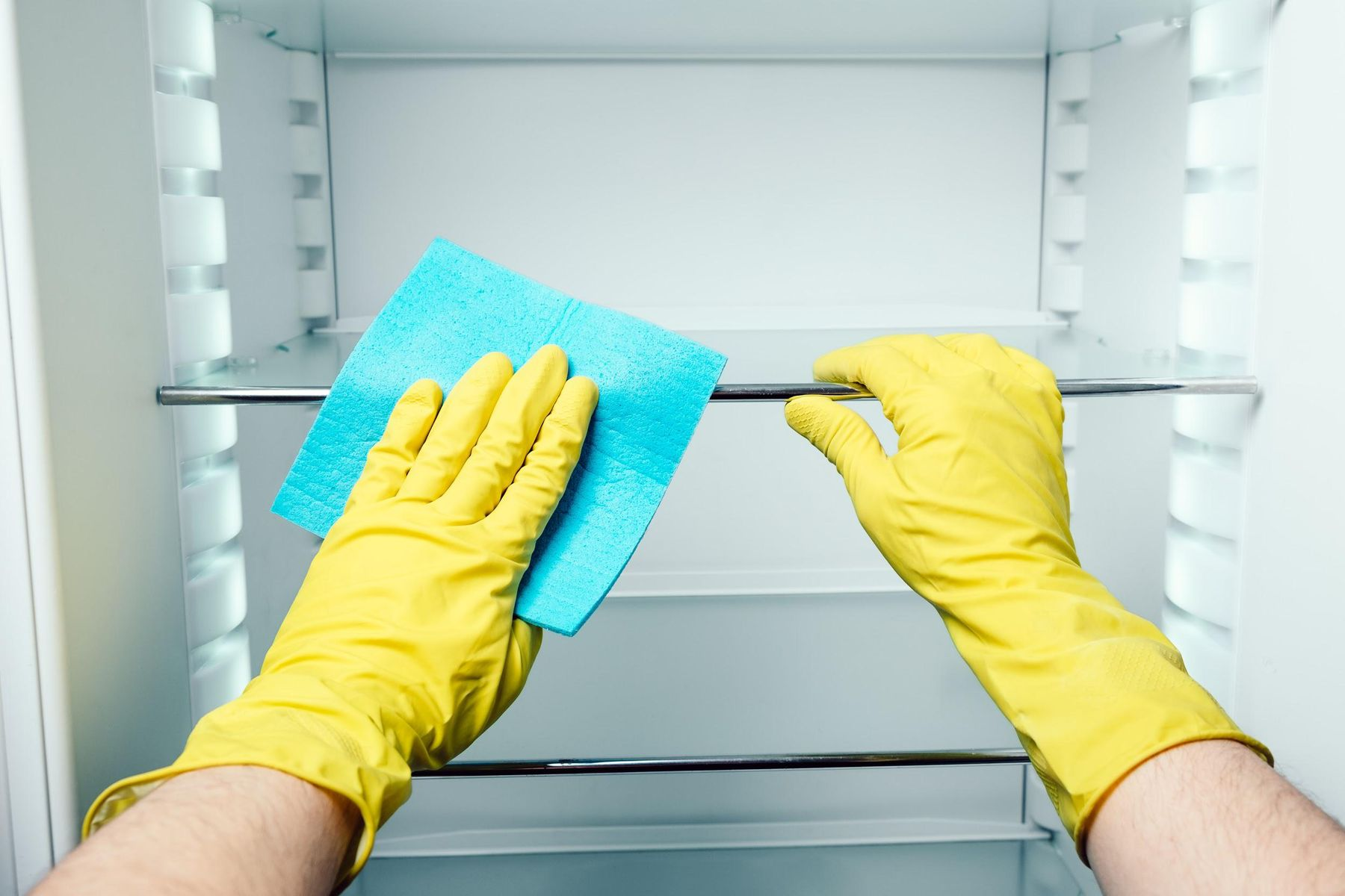 Mãos com luvas amarelas limpando as prateleiras da geladeira