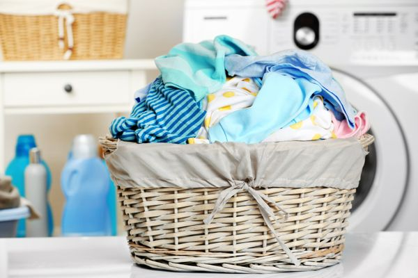 Mixed coloured clothes in a basket in front of a tumble dryer