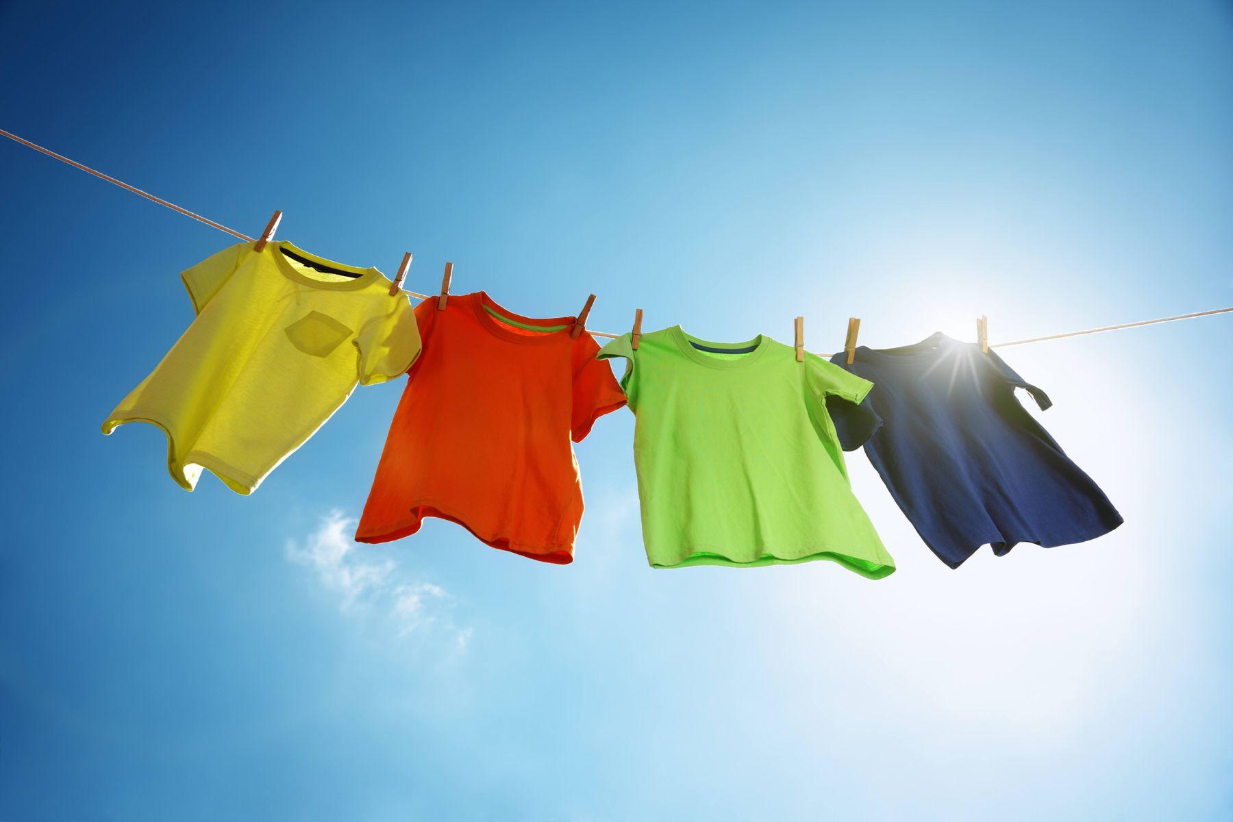 4 camisetas coloridas penduradas no varal com céu azul e sol ao fundo