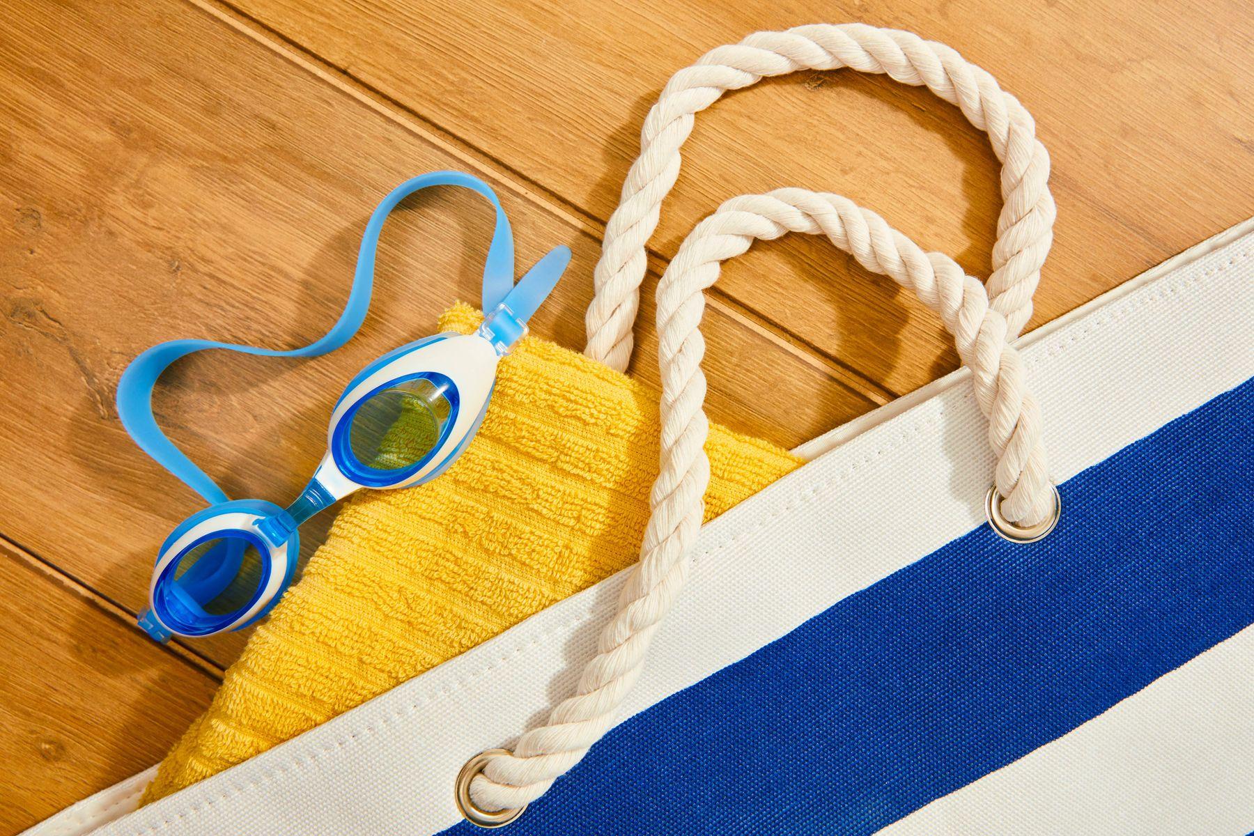 plaj havlusu ve yüzme gözlüğü içeren havuz çantası