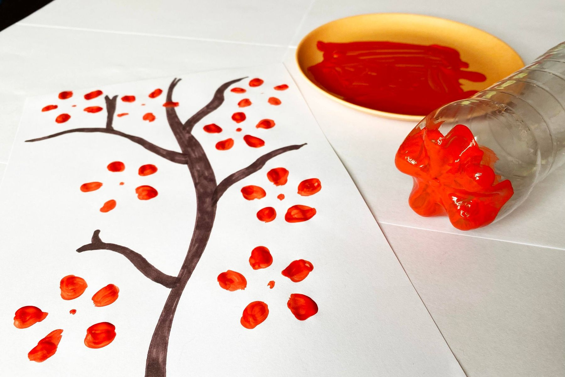 Using the bottom of  a plastic bottle to paint a blossom tree picture