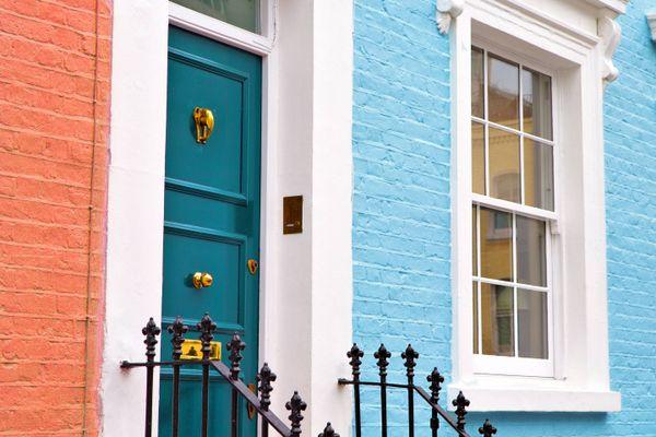 Die Vorderseite eines Hauses mit einer blauen Tür und gut bemalten Wänden und Fenstern.