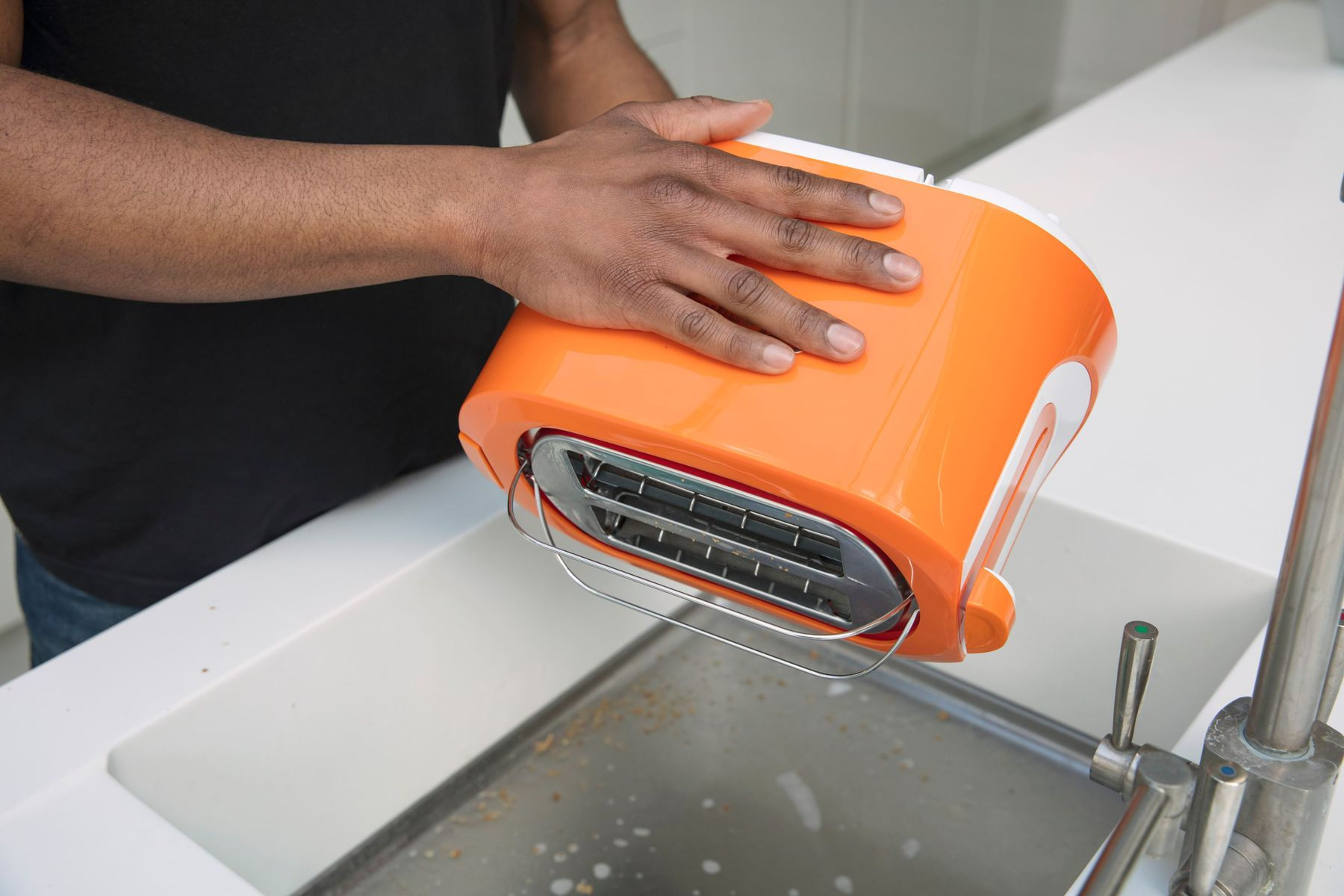Step 5: Emptying the bread crumbs from an orange toaster into a sink.