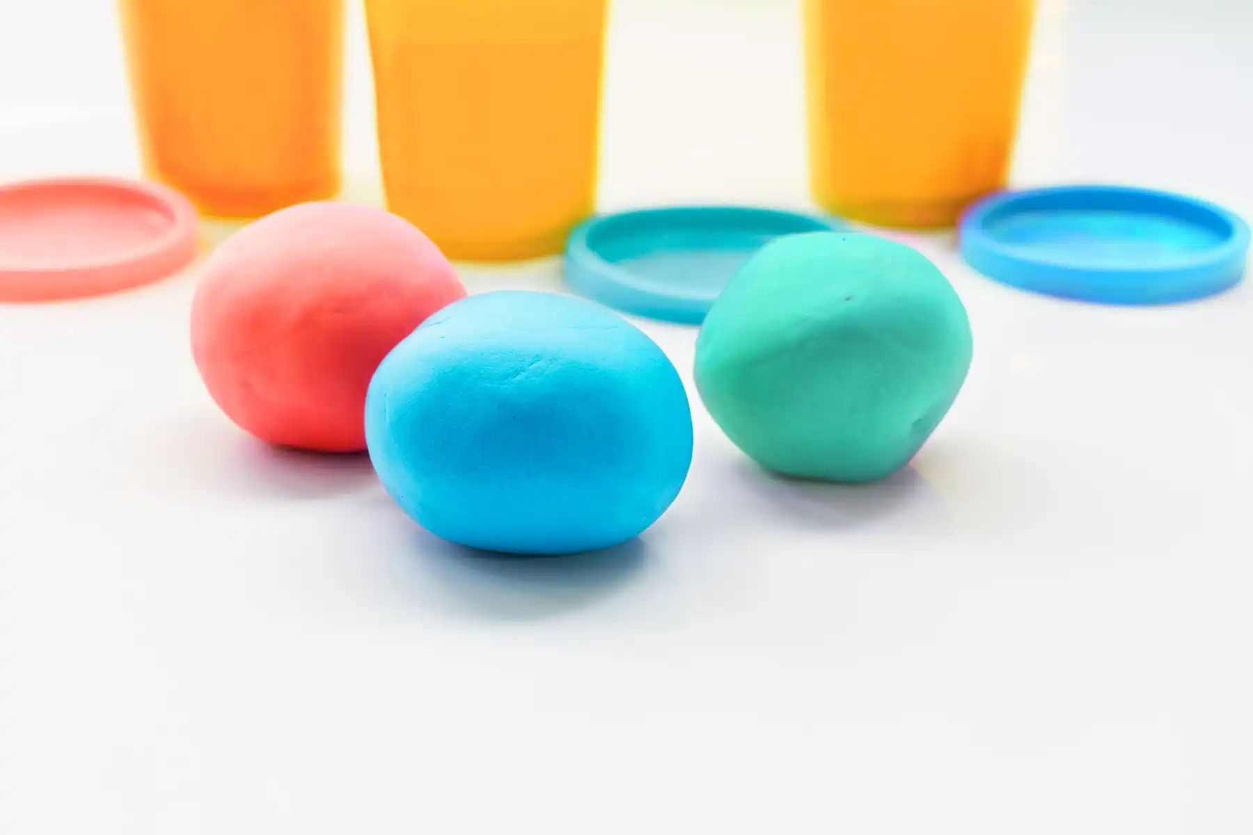 3 pots sit on a white surface with their lids beside them, with red, blue and aqua balls of playdough in front of them