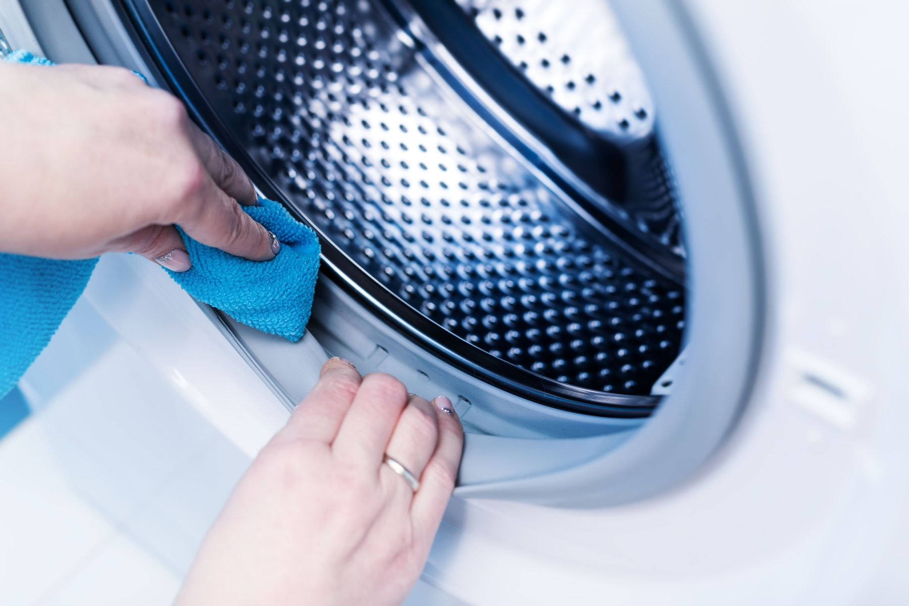 Pessoa limpando a parte interna da máquina de lavar de abertura frontal para tirar o mau cheiro