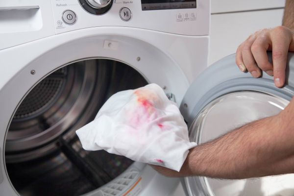 stained white clothing being put in washing machine to remove stain