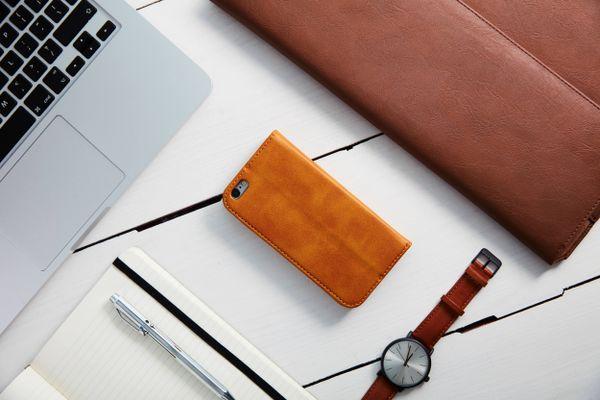 Telepon genggam bersarung kulit di sebelah benda dari kulit