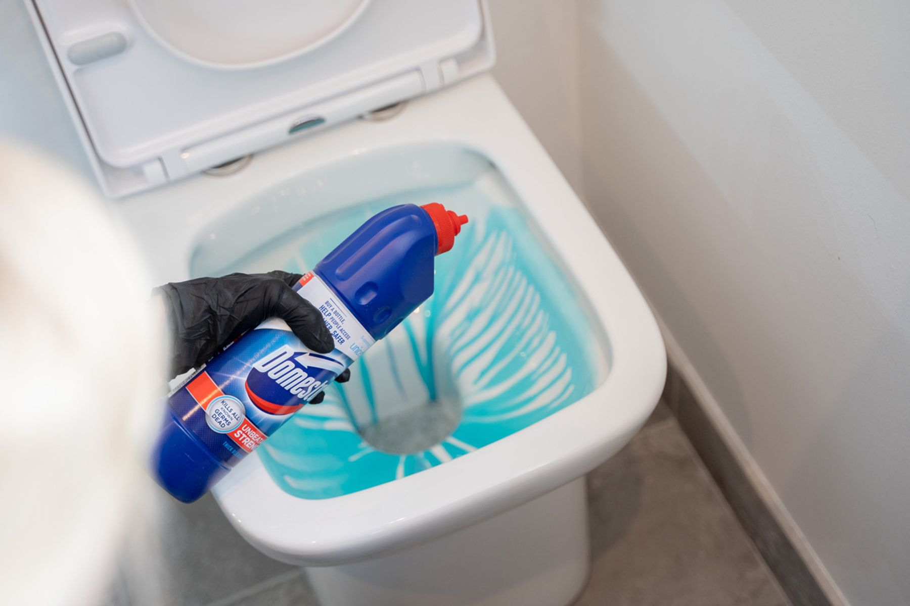 Step 1: Domestos being poured into a toilet bowl