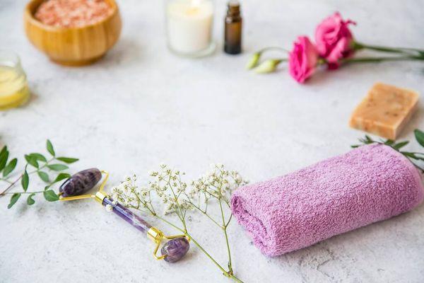 masajeador facial hecho de piedra amatista junto a una toalla de mano, una vela, un par de rosas y una botellita con aceite esencial